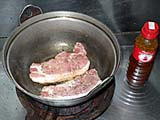 鉄鍋で豚をソテーする
