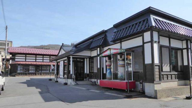 黒石 鶴の名湯温湯温泉共同浴場の外観 奥は湯治宿
